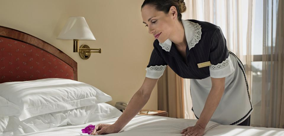 Maid-making-bed-in-hotel-room-smiling.jpg